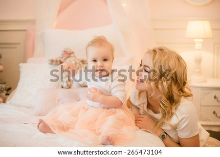 Mom and daughter playing on the bed, hugging