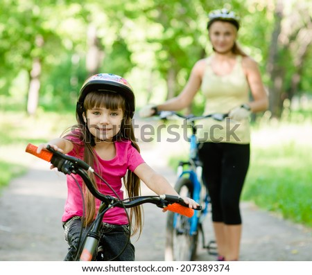 mom and daughter ride bikes in the forest - stock photo
