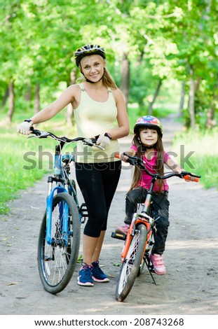 mom and daughter ride bikes in the park - stock photo