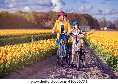 Mom and daughter riding bikes along tulip rows on a sunny day