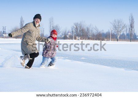 Mom and daughter running in the snow/running in the snow - stock photo