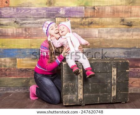 Mom and daughter smiling in multicolored studio interior - stock photo