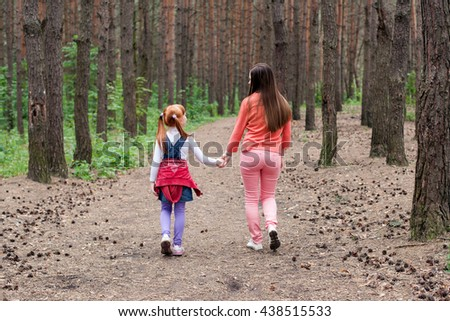 Mom and daughter walk along a forest road holding hands