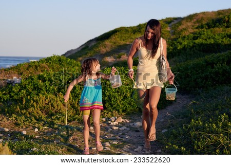 Mom and daughter walking after going fishing at the bach on a summer afternoon - stock photo
