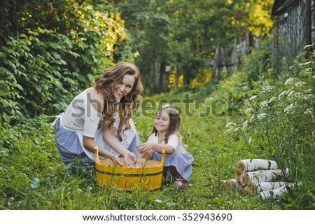 Mom and daughter washing clothes in a basin.
