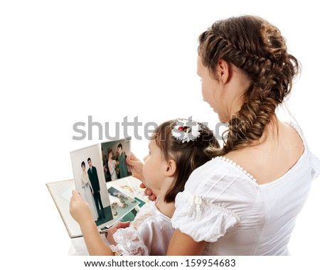 Mom and daughter watch family photo album.
