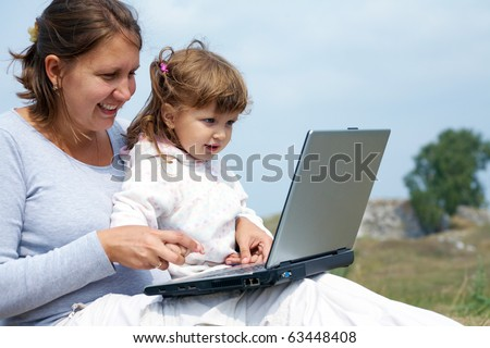 Mom and daughter working on laptop outdoors
