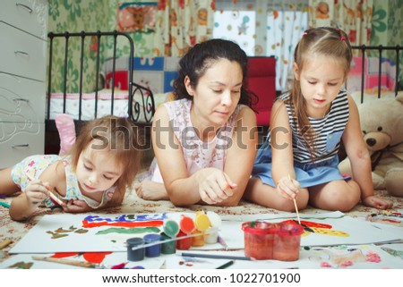 Mom and daughters painting pictures and lying on floor