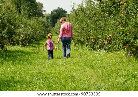 mom and girl walking through an orchard - stock photo