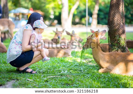 Mom and her child in the zoo - stock photo