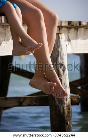 Mom and her child sitting on the wooden pier in the water and enjoying summer day. Bare feet of mother and her kid. Vacation by the sea. Outdoors.  - stock photo