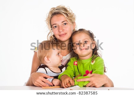 mom and her children drawing at table - stock photo