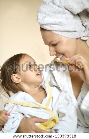 Mom and her little daughter in white bathrobes - stock photo