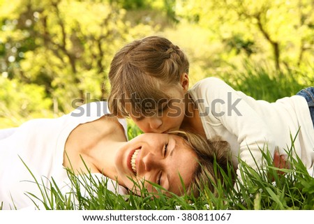 Mom and her little daughter lie on the grass