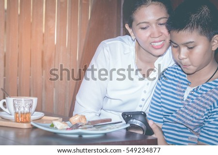 mom and her  son are using a smartphone