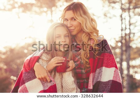 Mom and her 9 years old daughter spending weekend, picnic in the autumn forest together. Mother and child relations.