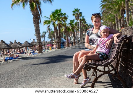 Mom and her young child sitting together on the bench in palm tree walkway near the beach. Copyspace. Tenerife, Canary