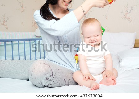 Mom and kid playing on the bed, smiling and laughing. Mother tickling child. Happy parents. Happy mother, happy baby. - stock photo