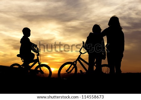 Mom and kids bond at sunset.