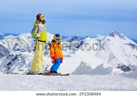 Mom and little boy mountain ski standing on top of the peak piste with high mountains on background