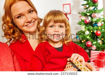 Mom and little daughter sitting by Christmas tree