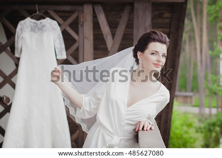 mom and little girl help the bride to wear a wedding dress. morning bride