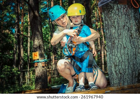 Mom and little son in the outfit have been climbing the trees. Mom and young son  in a special outfit studying climbing the trees - stock photo