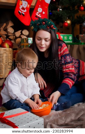 Mom and son eating corn sticks under the Christmas tree and fireplace - stock photo