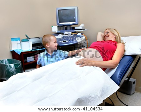 Mom and son enjoy a moment of joy as they wait for an ultra sound of new baby coming.  Little boy's hand is on mommy stomach and they are smiling at each other.