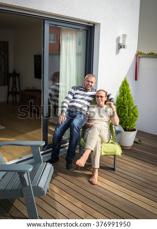 Mom and son enjoying in yard front of the house - stock photo