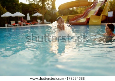 Mom and son having fun in the summer playing in the pool - stock photo
