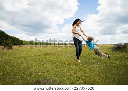 Mom and son in the summer field. Mother playing with her son. Mother and son having a great weekend. Games, field, family weekend - family-friendly concept. Article about the family. - stock photo