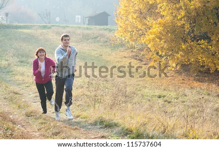 Mom and son jogging in a meadow - stock photo