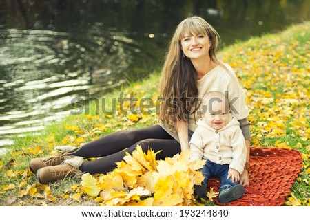 Mom and son on a autumn park background