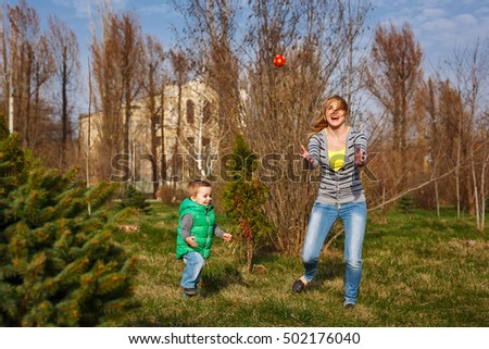 Mom and son playing ball in the autumn park. Family time. Happiness of childhood and motherhood. Active leisure on the open air.