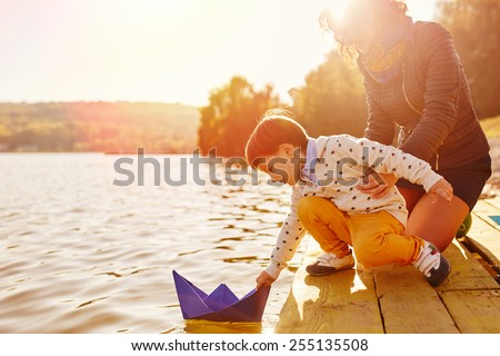 Mom and son playing with paper boats by the lake. Warm filter and film effect - stock photo