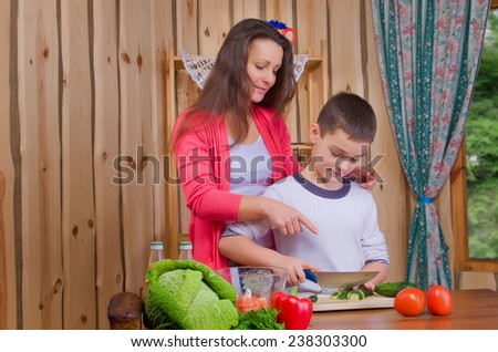 Mom and son preparing food in the kitchen - stock photo