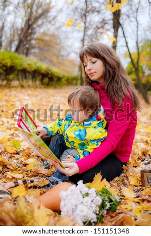 Mom and son  reading a book. autumn park - stock photo