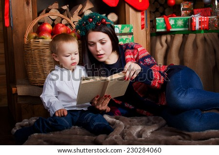 Mom and son reading a book in a Christmas setting
