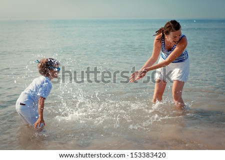 Mom and son splashing water at sea, outdoor