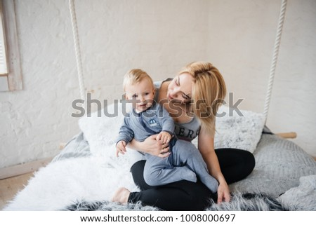 Mom and son with blond hair. A room in Scandinavian style. Near the window. They embrace, they play in their pajamas. Suspended bed.