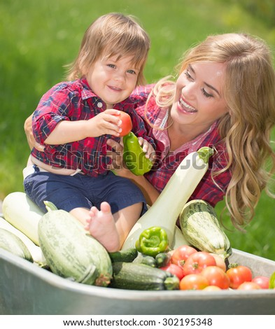 mom and son with vegetables harvest in garden. little boy sitting in the wheelbarrow
