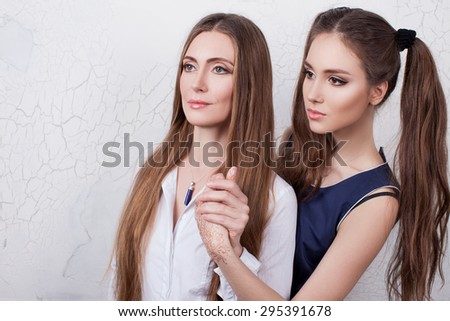 Mom and teenage daughter. Concept of happy family.Mother and daughter look to one side and hold hands, studio, light background. A young girl and her mother looking in profile .Mother and daughter - stock photo