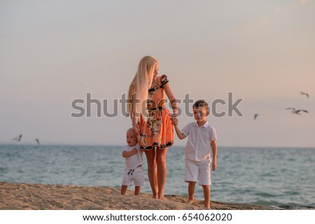 Mom and two little sons on the beach. Meet the sunset