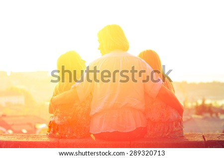 Mom and two sisters twins sitting on the parapet and watch the sunset. Family vintage composition