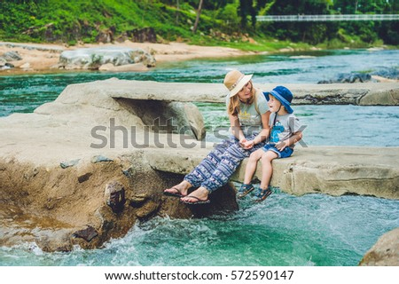 Mom and young son sitting on bridge on a background of the river. Traveling with kids concept