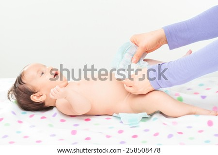 Mom changing diaper her little baby girl. Copy space above - stock photo