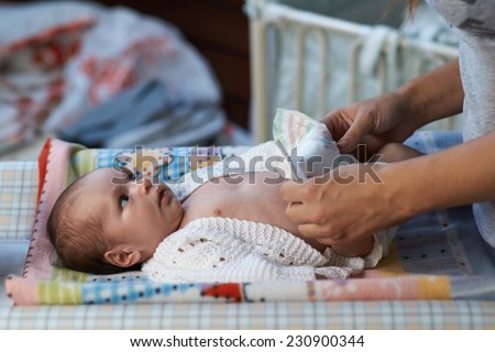 mom changing diapers newborn baby - stock photo