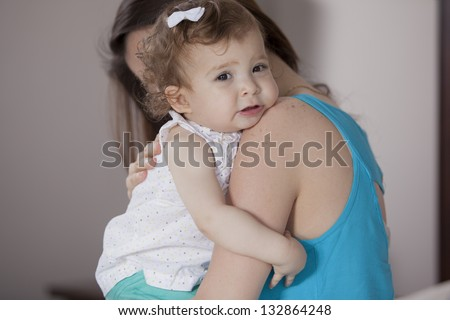 Mom comforting her baby girl - stock photo