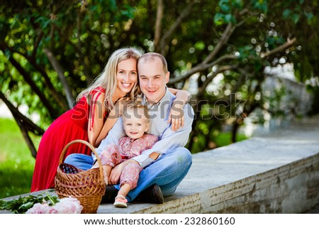 Mom, dad and charming girl smiling in the background trees - stock photo